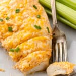 A baked buffalo chicken breast with one bite on a fork