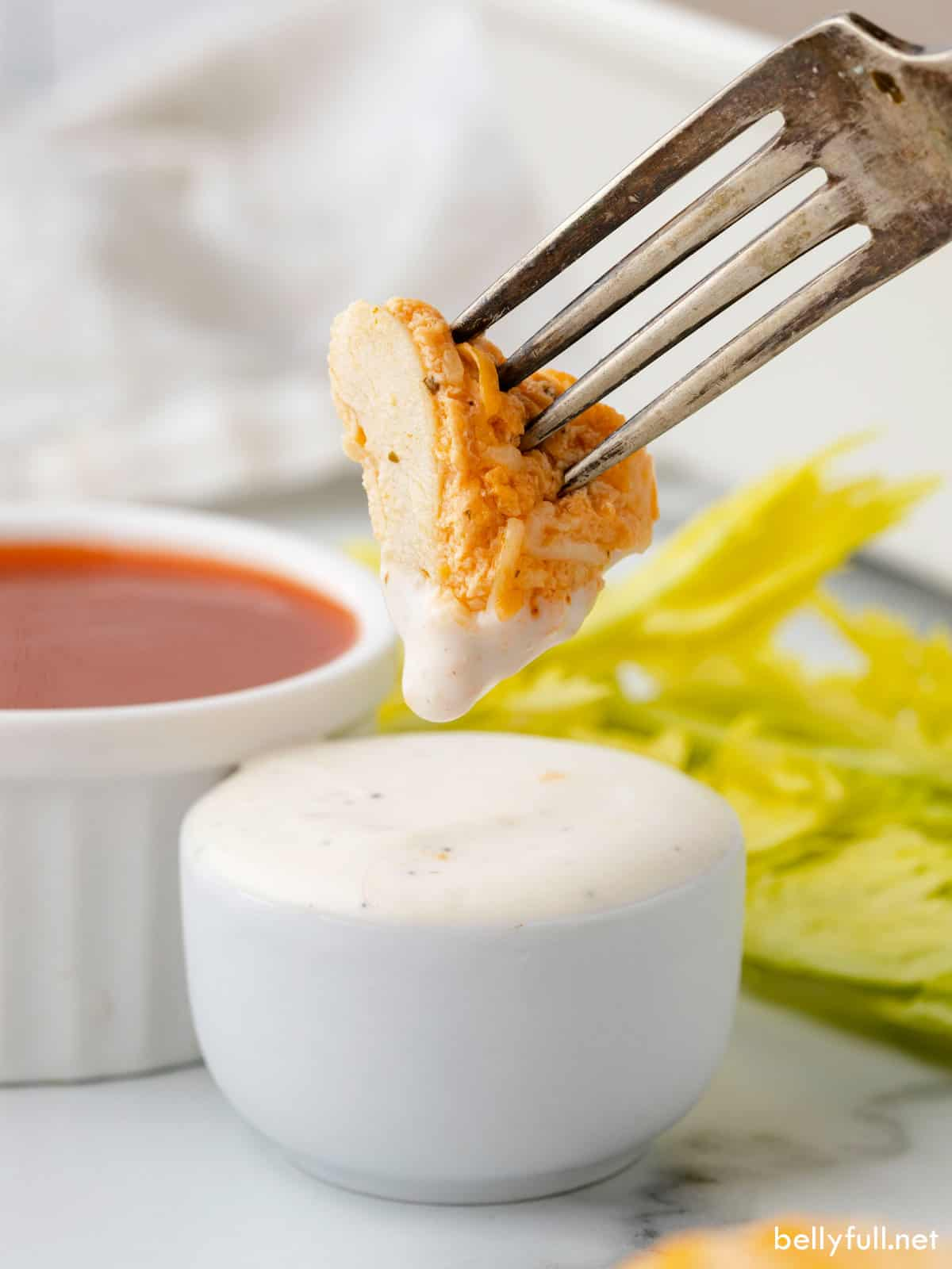 A piece of buffalo chicken breast on a fork dipped in ranch dressing