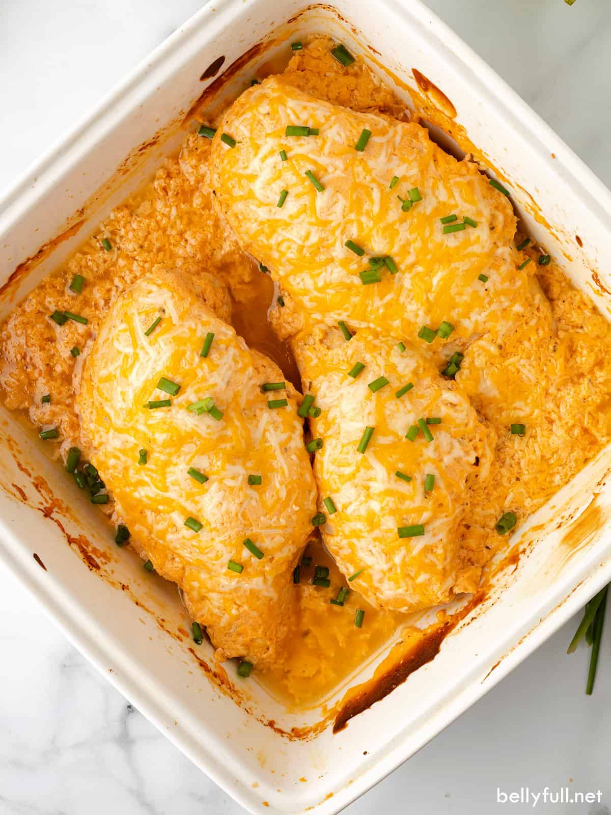 Buffalo chicken breasts in a baking dish topped with lots of cheese