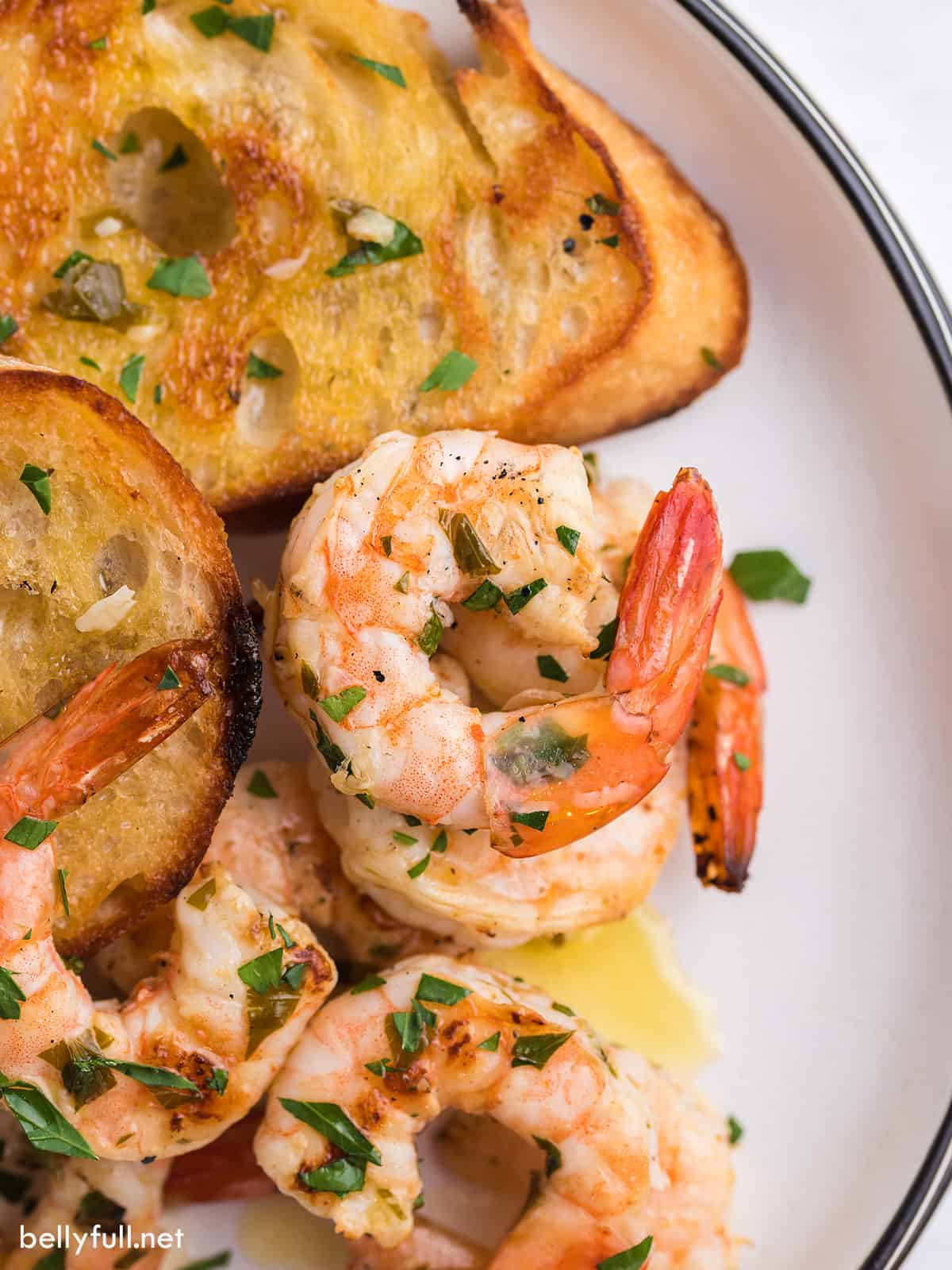 A close up of grilled shrimp scampi and baguette slices on a plate