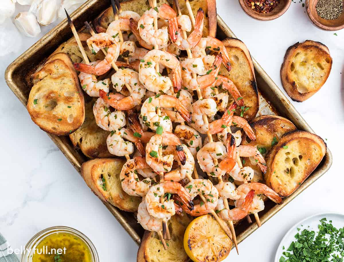 A sheet pan of grilled shrimp and baguette slices