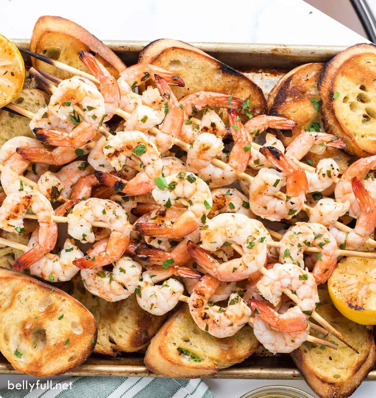 Grilled shrimp skewers on top of grilled baguette slices