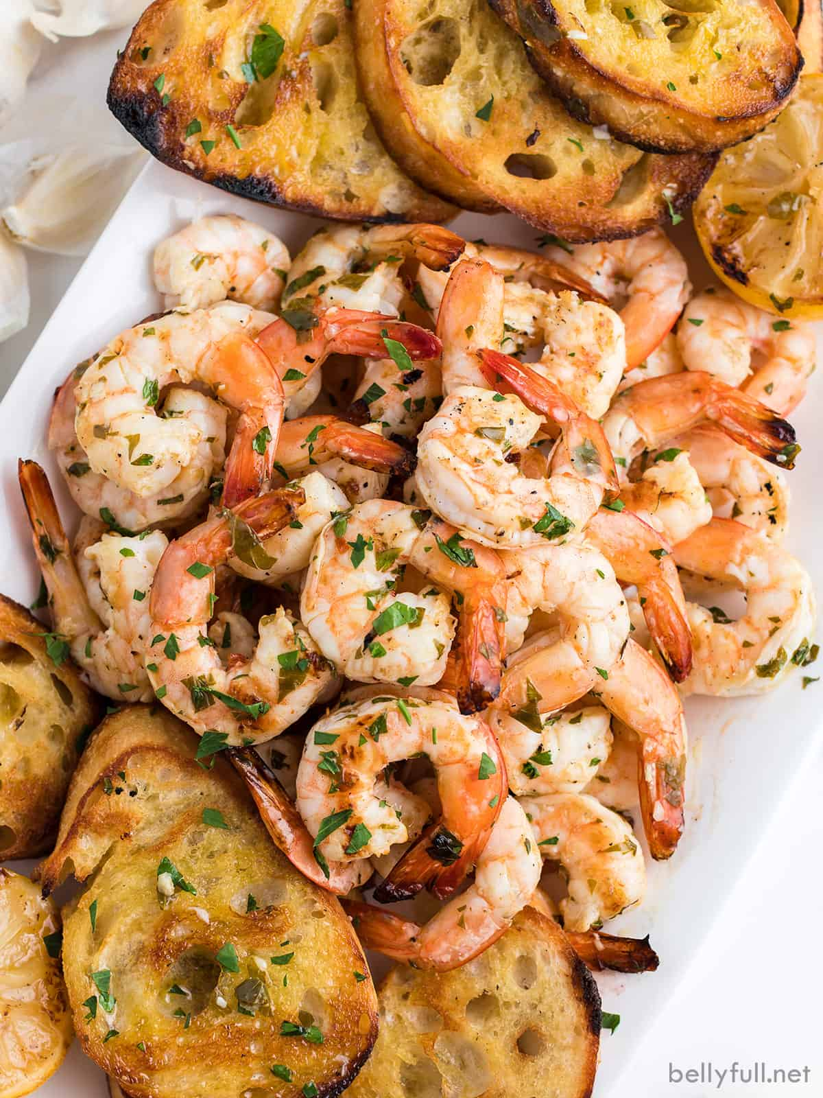 Grilled shrimp scampi on a serving tray with baguette slices