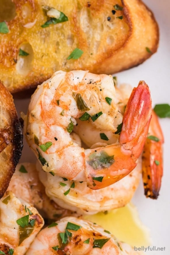 close up grilled shrimp with butter and parsley