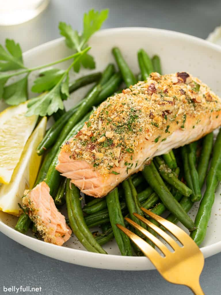baked salmon on top of green beans with bite taken