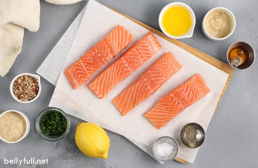 4 fresh raw salmon fillets on parchment paper