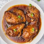 overhead honey garlic chicken thighs coated in sauce on white plate