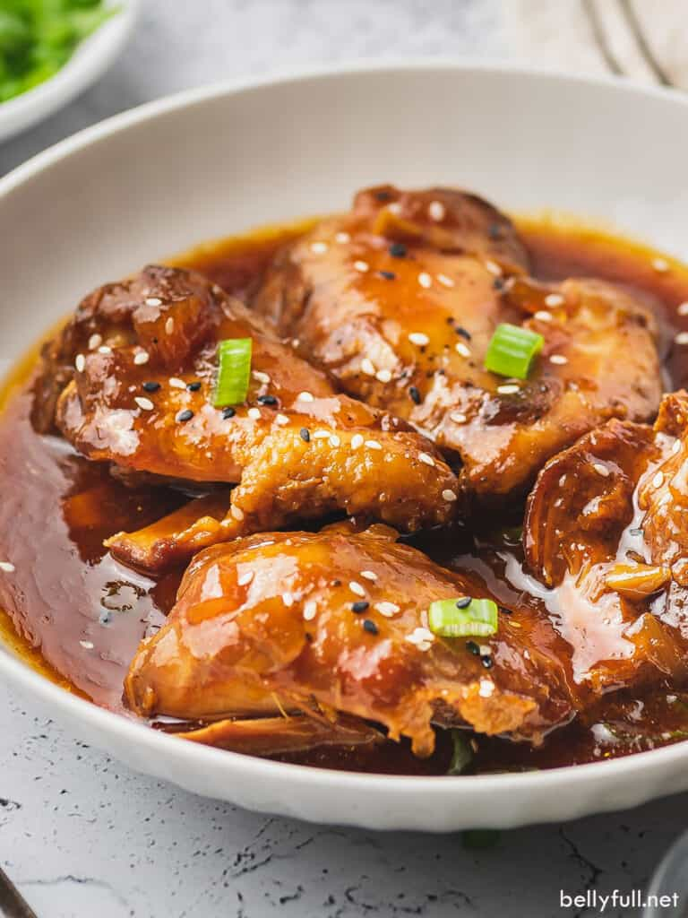 glazed chicken thighs coated in sauce in white bowl
