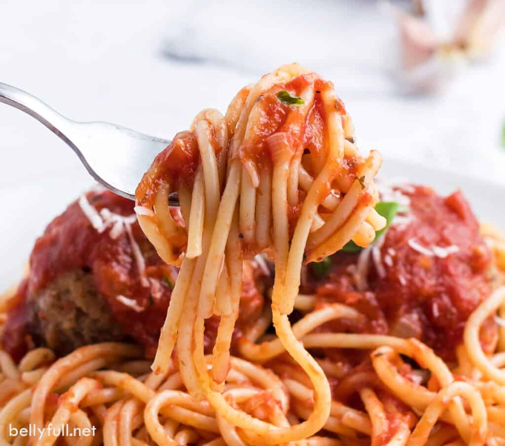 close up spaghetti with sauce hanging off of fork