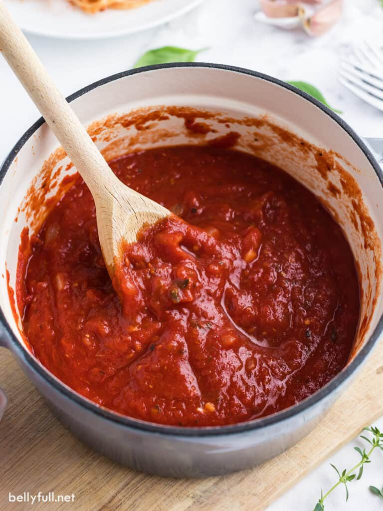 marinara sauce in saucepan with wooden spoon