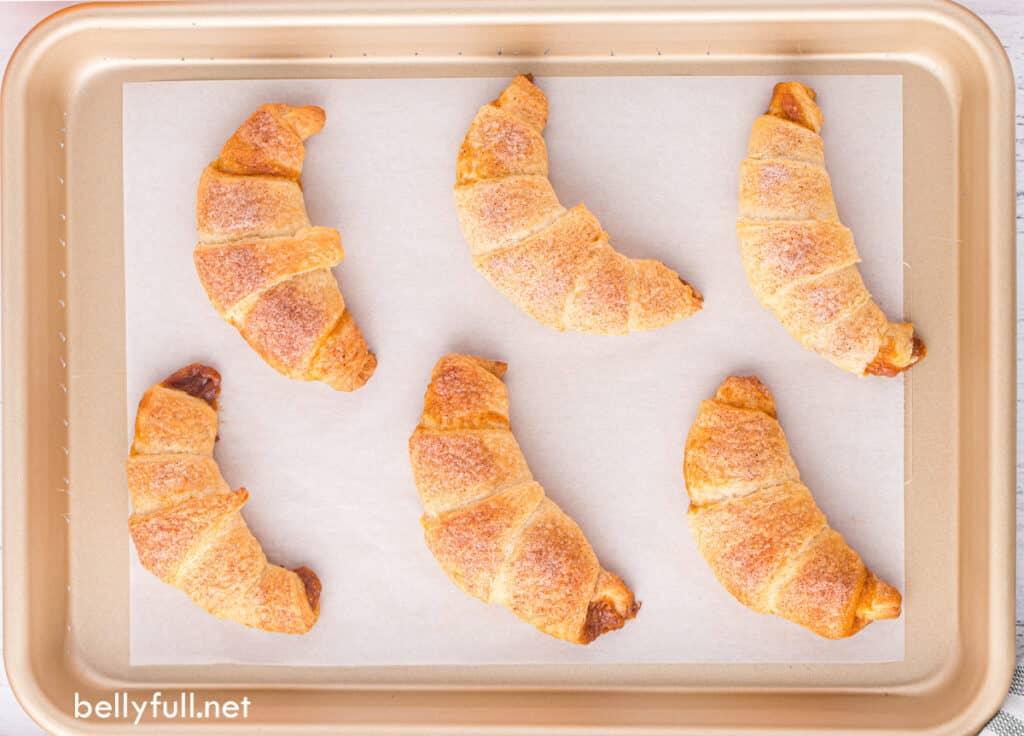 6 baked moon shaped crescent rolls on baking sheet
