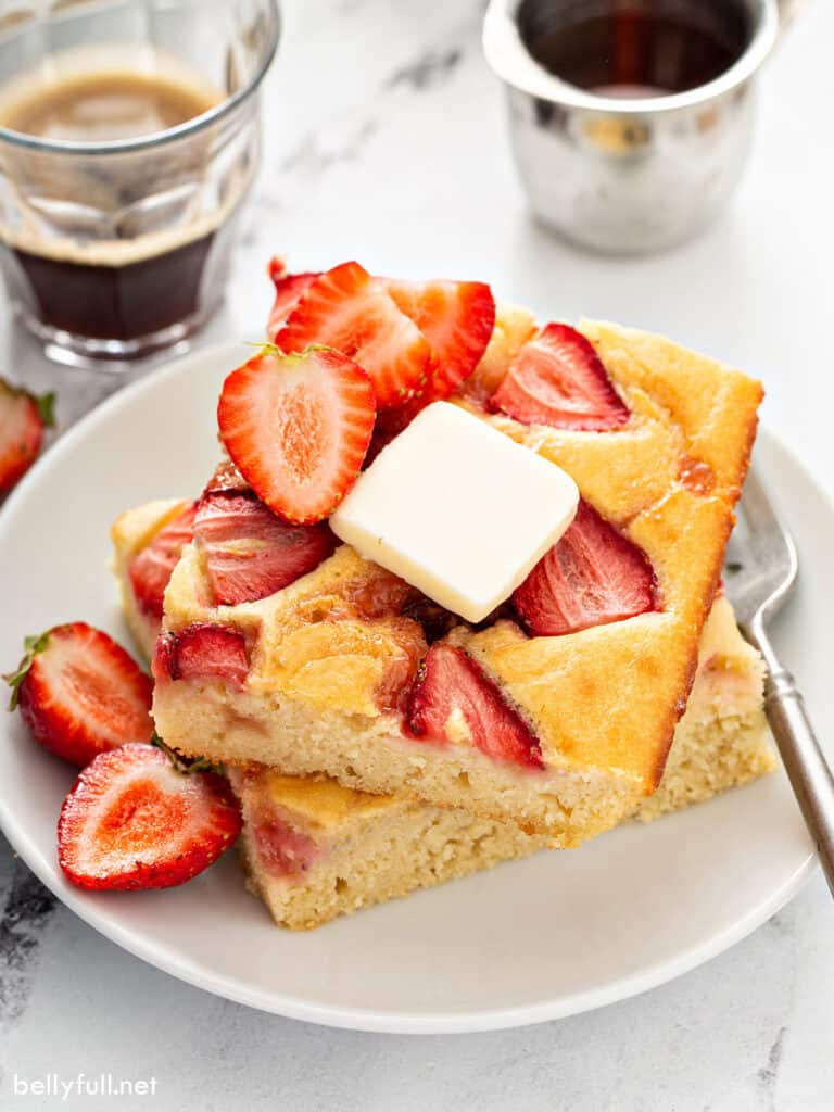 2 square strawberry pancakes stacked with a slab of butter on top