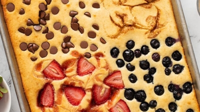 sheet pan pancakes divided into 4 sections with berries, chocolate, and cinnamon