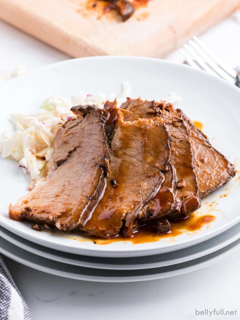 5 slices of brisket with barbecue sauce on white plate