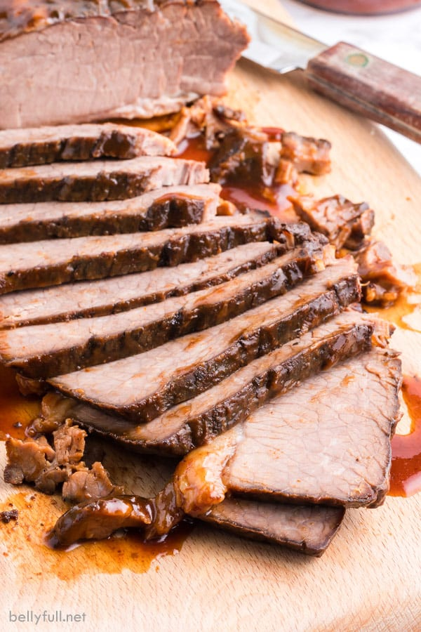 slow cooker beef brisket sliced thin on cutting board