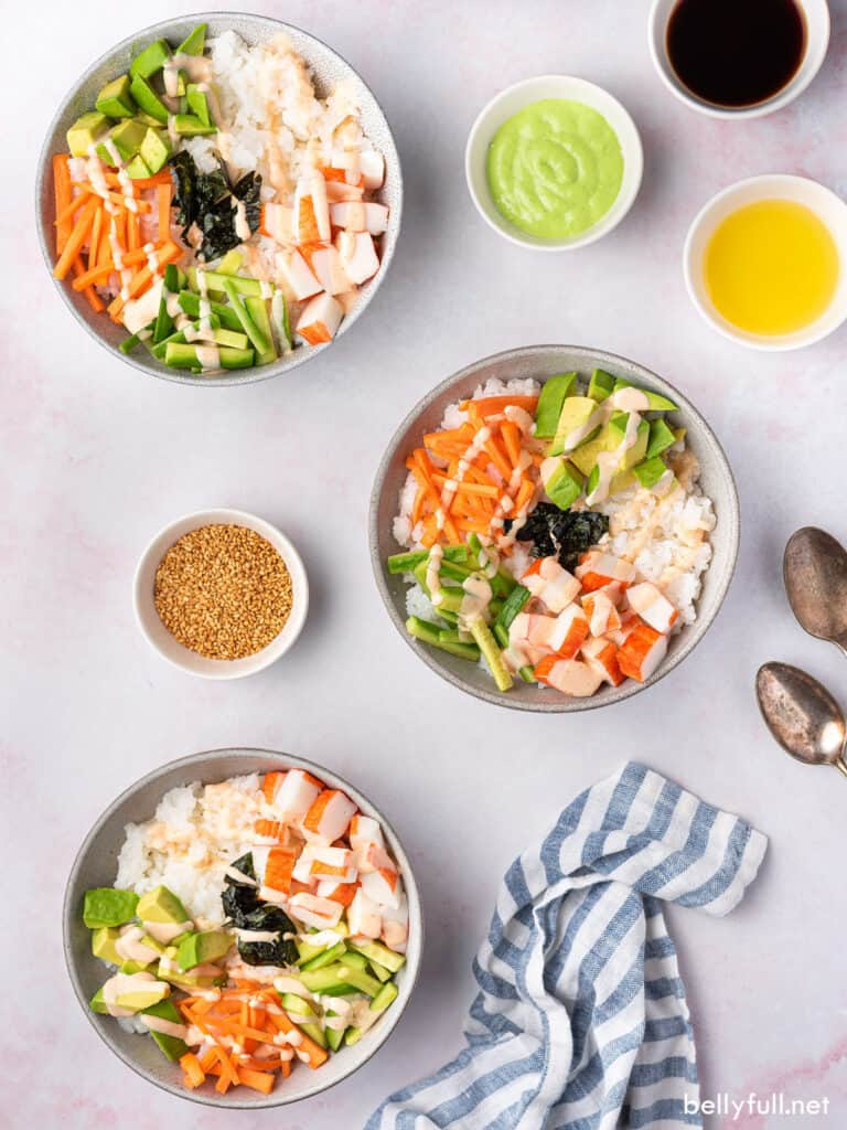 overhead of 3 bowls filled with sushi rice, carrots, cucumber, avocado, and crab