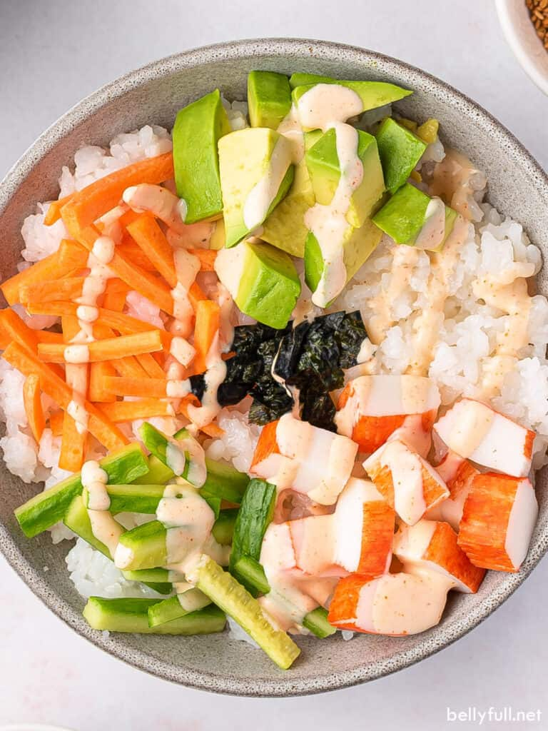 close up overhead sushi bowl with carrots, cucumber, avocado, and crab
