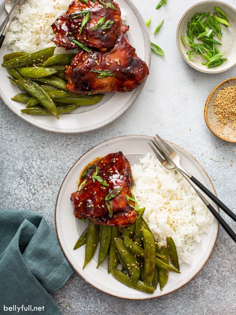 overhead glazed chicken thighs on plate with white rice and snap peas