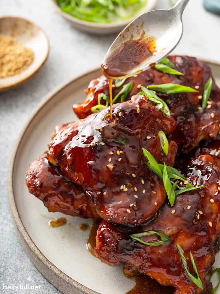 spoonful of Teriyaki sauce dripping onto baked glazed chicken thighs