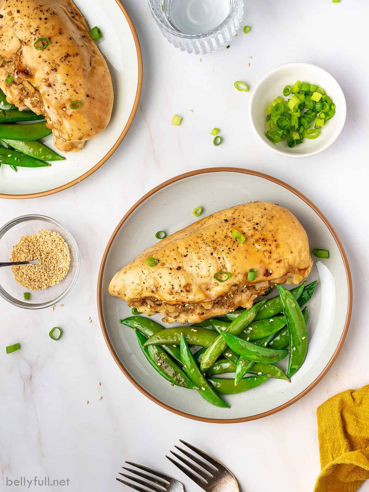 Overhead view of a stuffed chicken breast on a plate with green beans