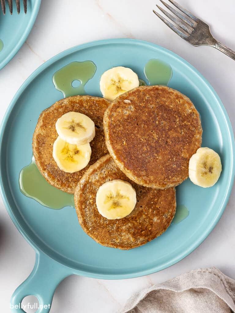 3 banana oatmeal pancakes on plate with banana slices