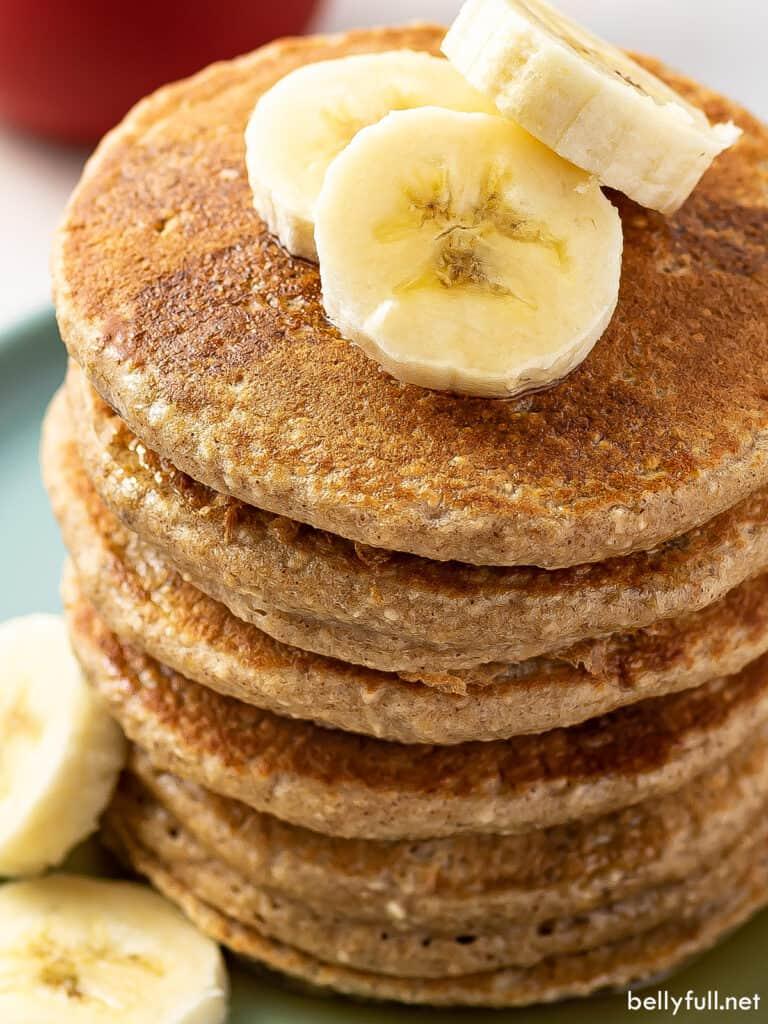stack of 6 banana oatmeal pancakes with sliced banana on top