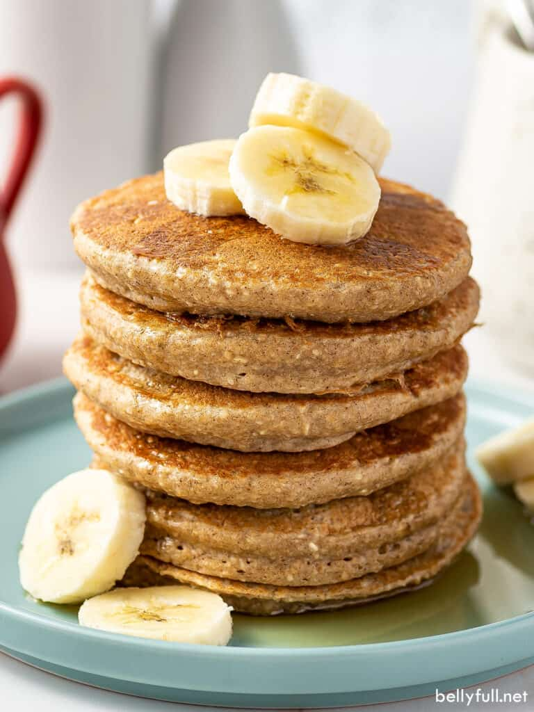 stack of 6 banana oatmeal pancakes with banana slices