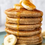 tall stack of banana pancakes with banana slices and maple syrup poured on top