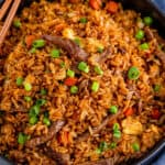 beef fried rice in black serving bowl with chopsticks