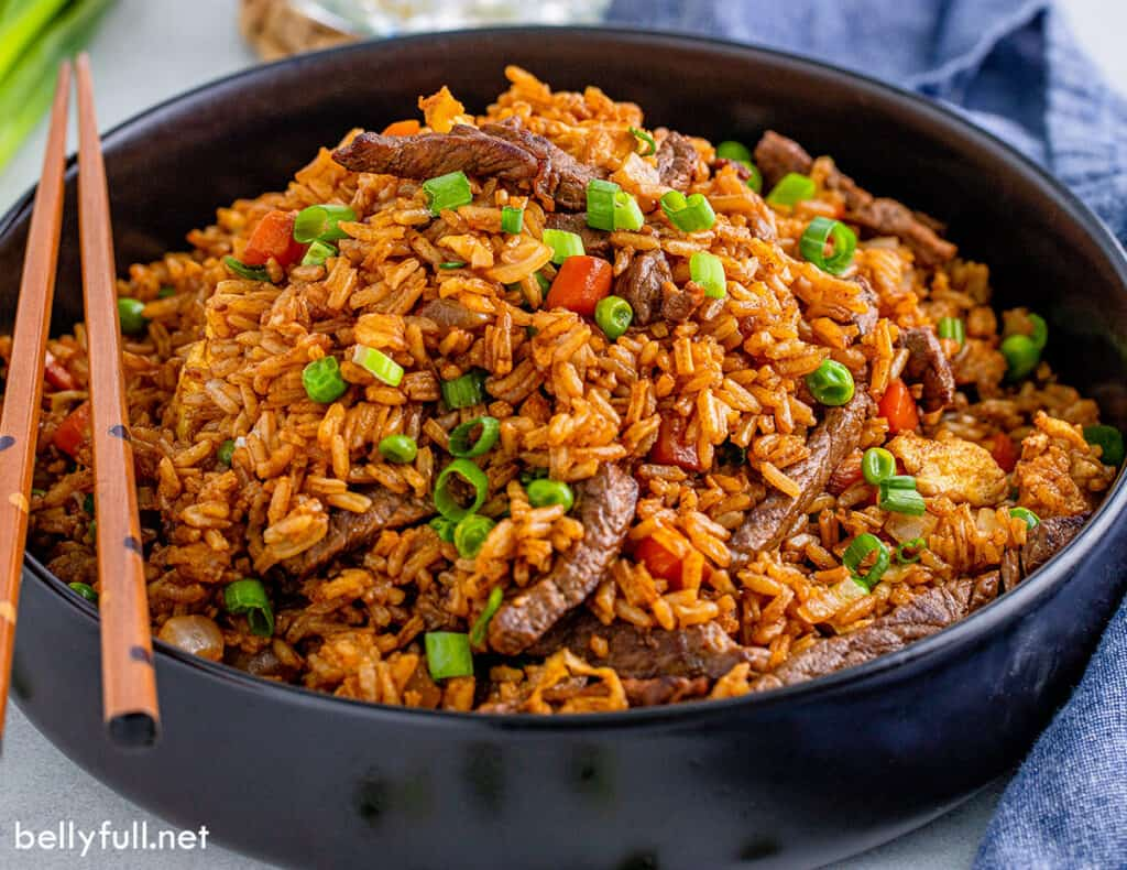 fried rice with beef and vegetables in black serving bowl with chopsticks