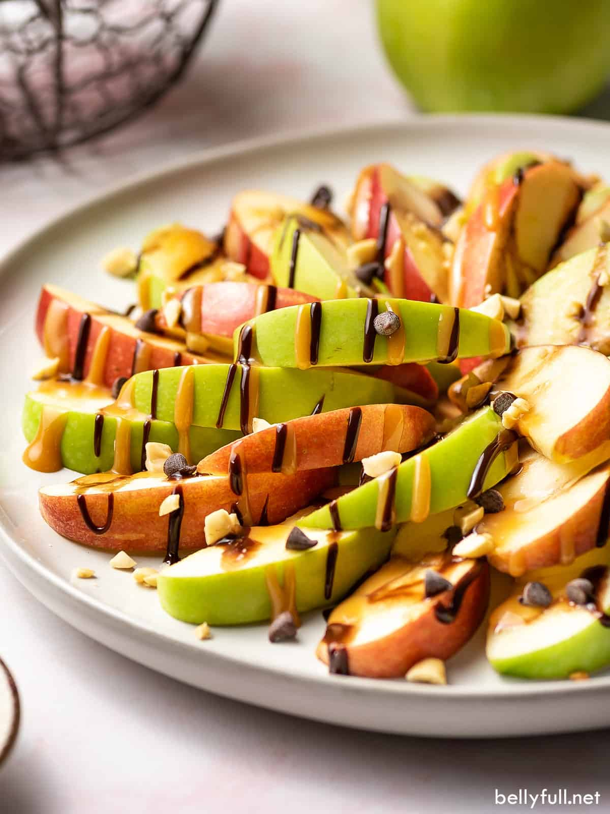 A plate of caramel apple nachos with hot fudge and caramel sauce