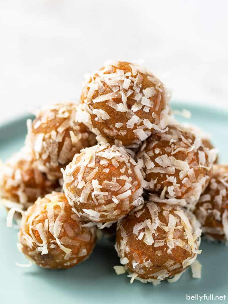 carrot cake energy balls coated in coconut flakes piled on a plate