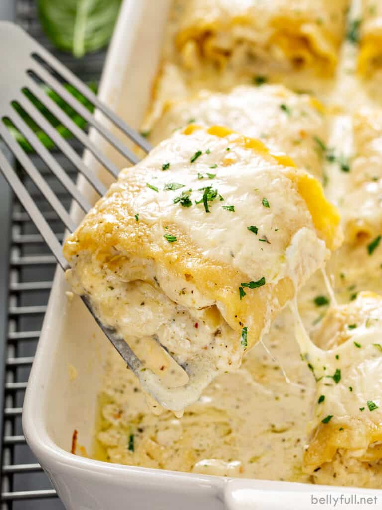 white chicken lasagna roll being lifted out of baking dish with spatula