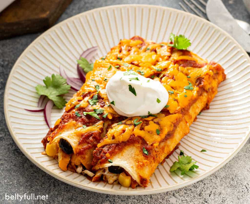 2 enchiladas with sour cream on plate