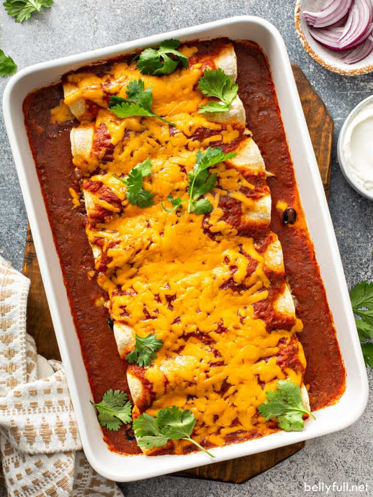 chicken enchiladas covered in melted cheddar cheese in baking dish