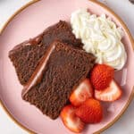 2 slices of glazed chocolate pound cake on pink plate with strawberries and whipped cream