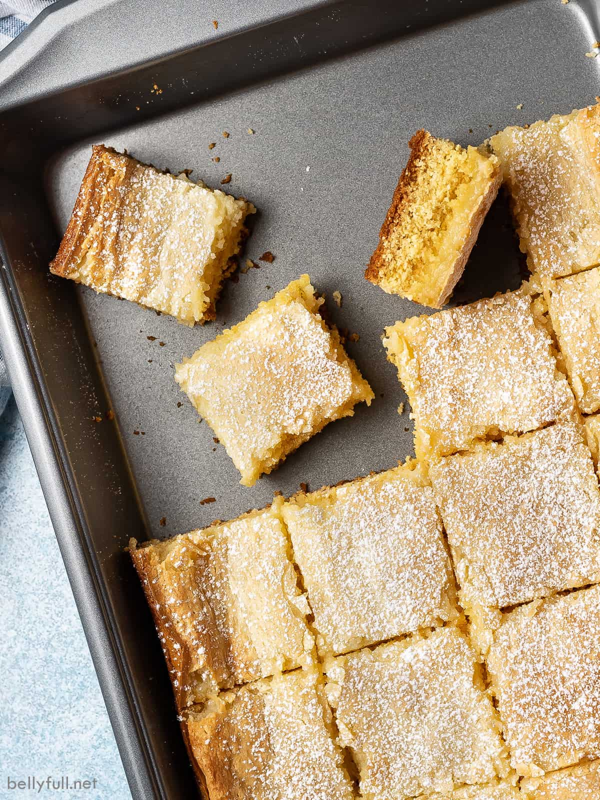 Gooey butter cake in a cake pan with some squares missing
