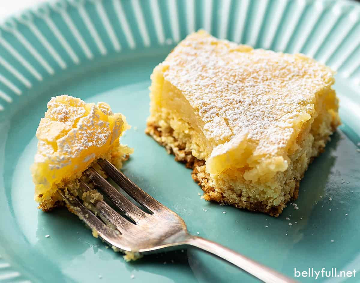 A slice of gooey butter cake on a plate with a fork