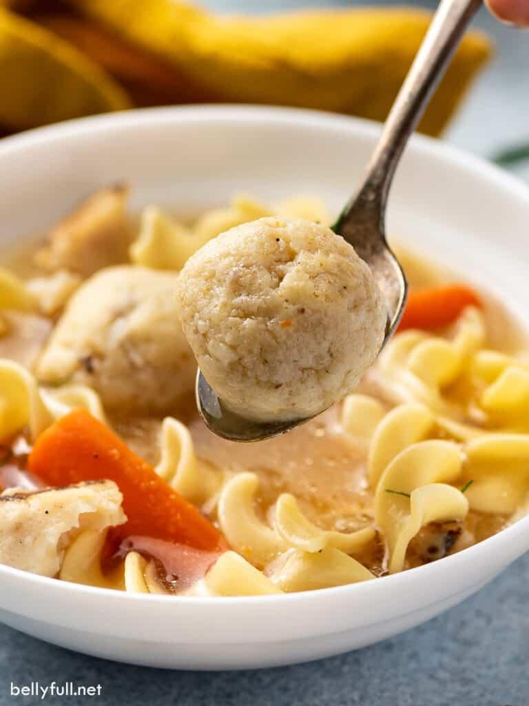 matzo ball on spoon over bowl of soup