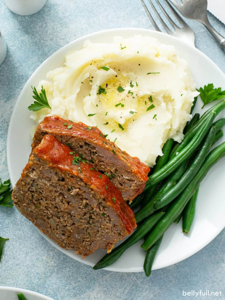 2 slices of meatloaf on plate with mashed potatoes and green beans