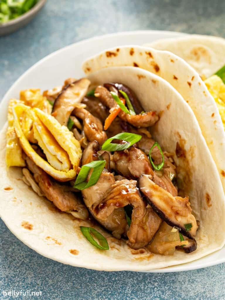 close up moo shu pork in flour tortilla cradled like a taco