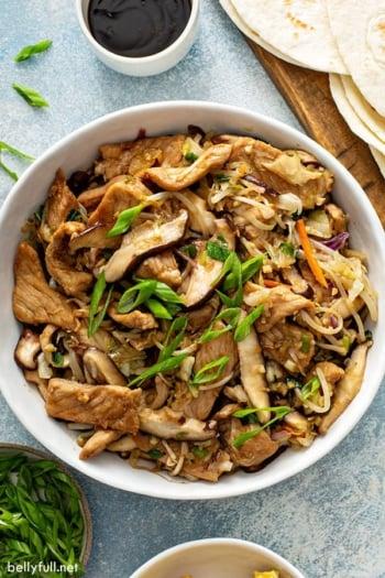 Moo shu pork stir fry in white serving bowl