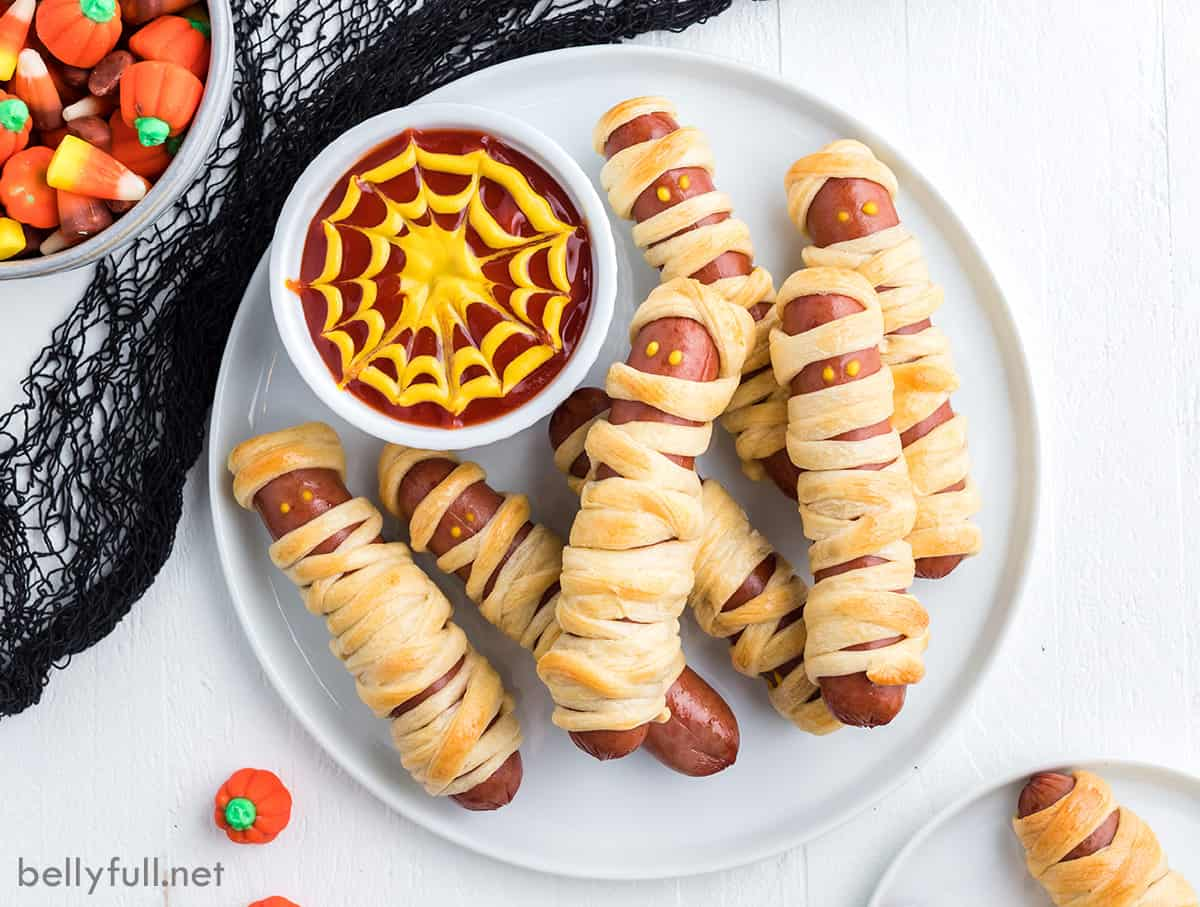 A plate of Halloween mummy hot dogs on a plate with spiderweb sauce