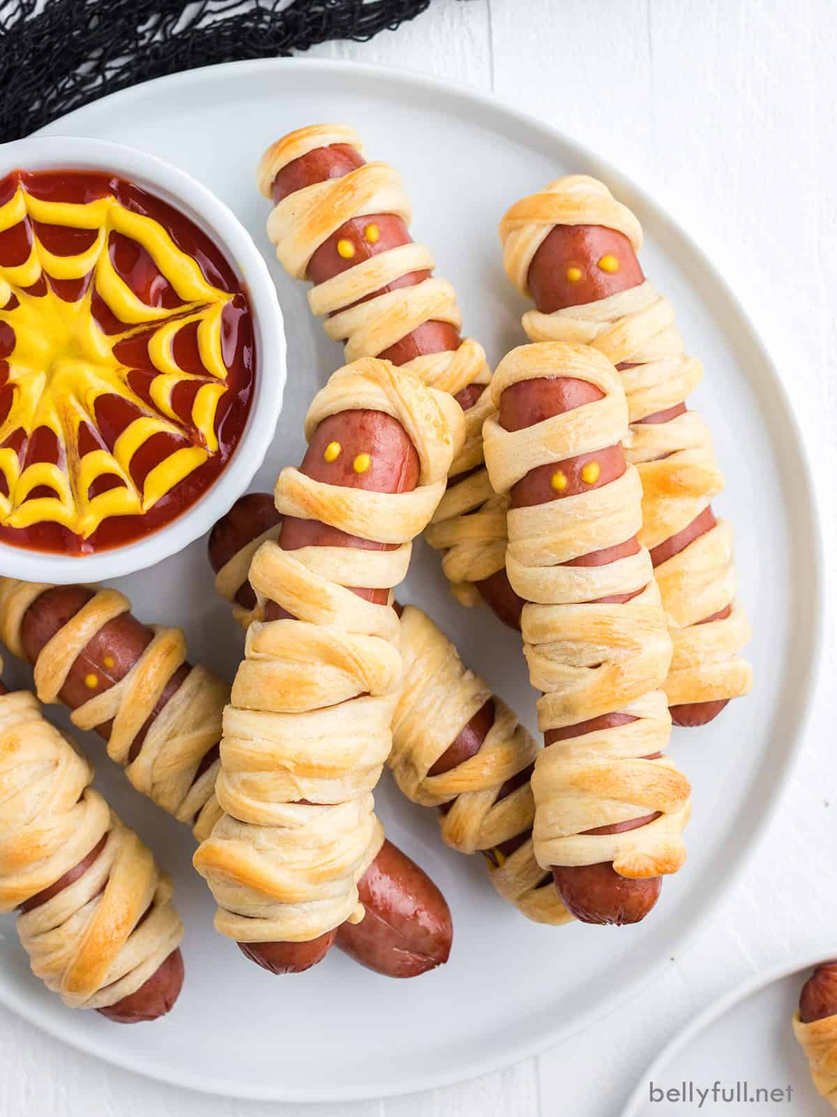 Mummy dogs on a white plate with spiderweb sauce