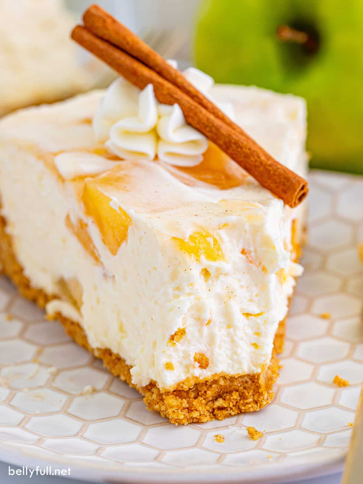 A slice of apple pie cheesecake on a plate with a bite missing