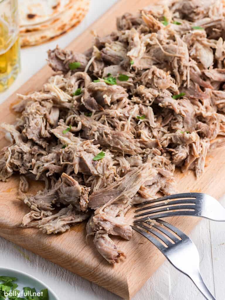 shredded pork on cutting board with 2 forks