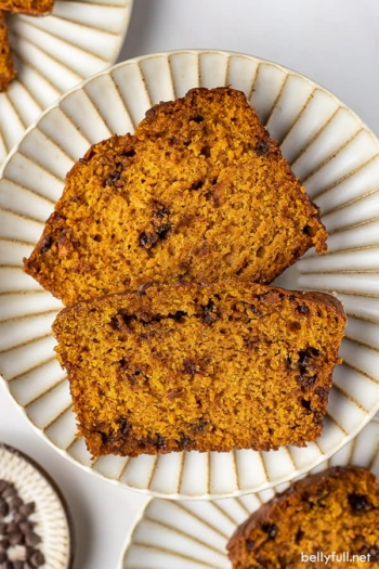 Overhead view of two slices of pumpkin chocolate chip bread on a white plate