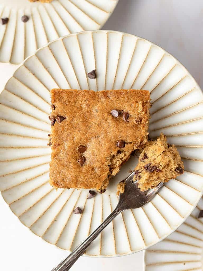 square piece of cake with mini chocolate chips on plate with fork