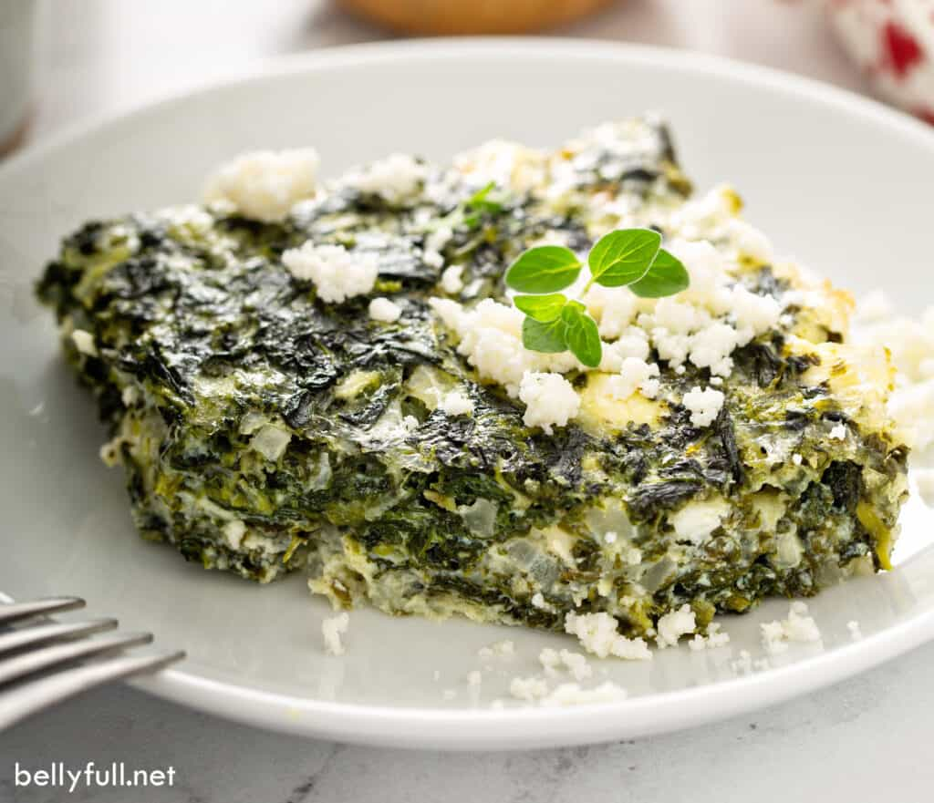 slice of baked spinach and feta cheese casserole with bite taken
