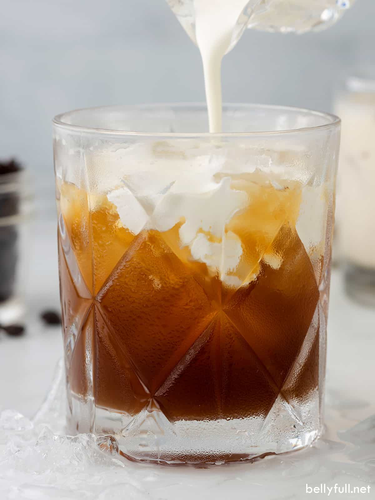 Cream being poured into a Black Russian cocktail to make a White Russian